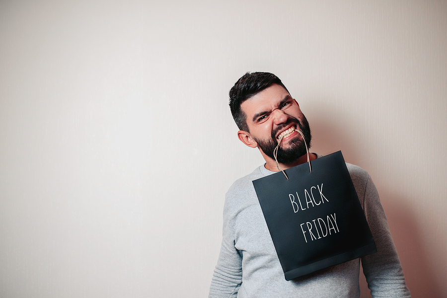 Man holding shopping bag in mouth looking for Black Friday tips to avoid debt