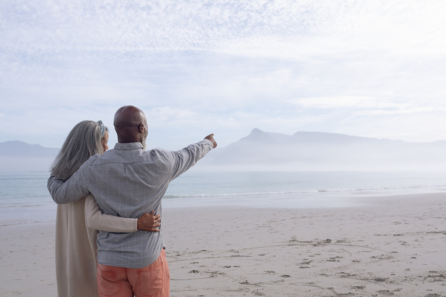 Couple on beach overlooking ocean enjoying retirement thanks to retire planning and credit counselling