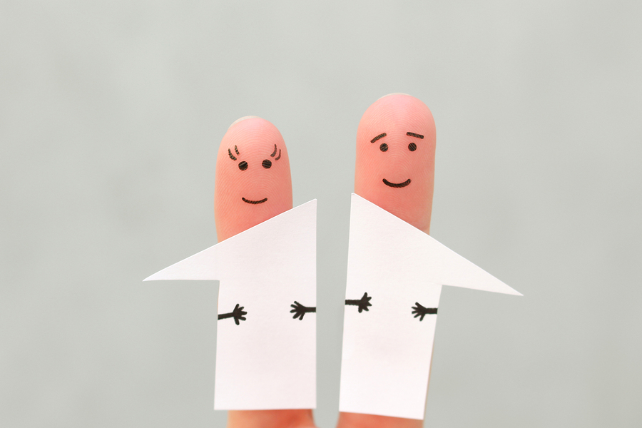 Two fingers with faces splitting divorce debt, assets, and joint debt equally between one another during a divorce