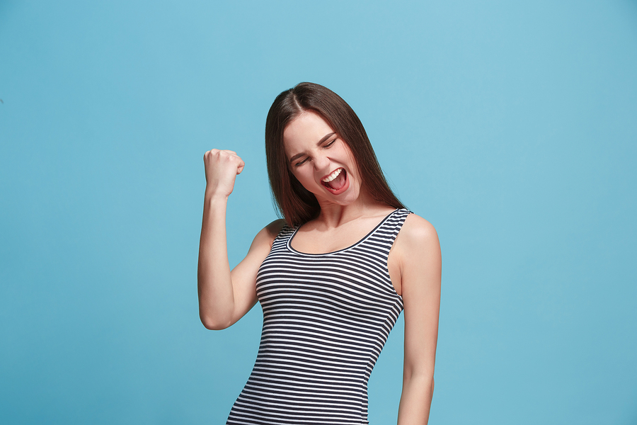 Woman in striped shirt happy about reducing her debt and avoiding financial difficulties