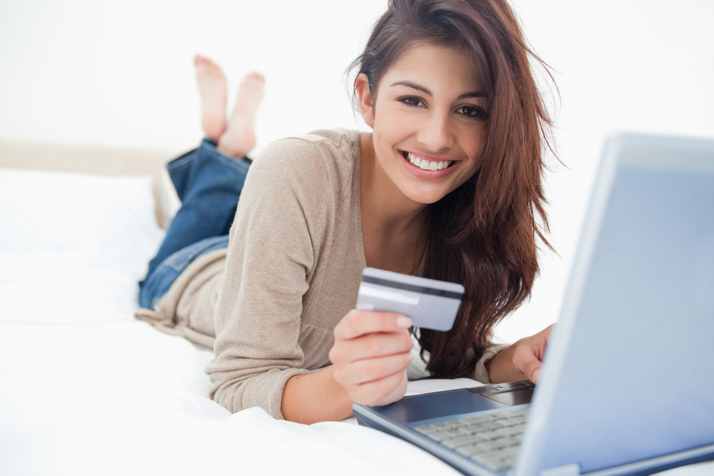 Young woman on a laptop reading the Credit Card Handbook about the proper use of credit cards