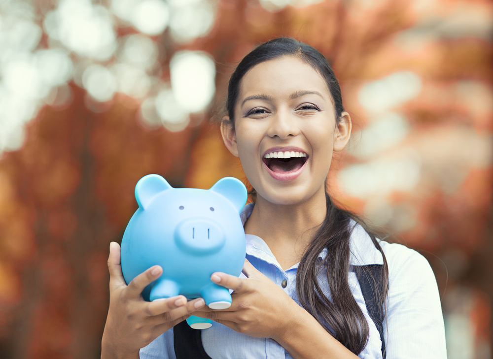 Young woman holding blue piggy bank with savings from smart budgeting and money management