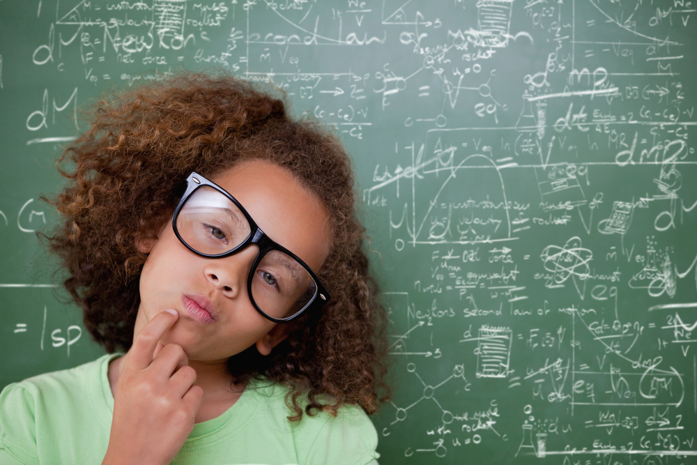 Child wearing glasses and in green in front of chalk board determining best way for getting out of debt