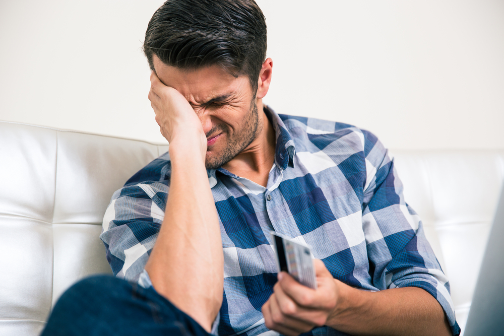 Young man devastated about credit card balance and cost of credit card rewards
