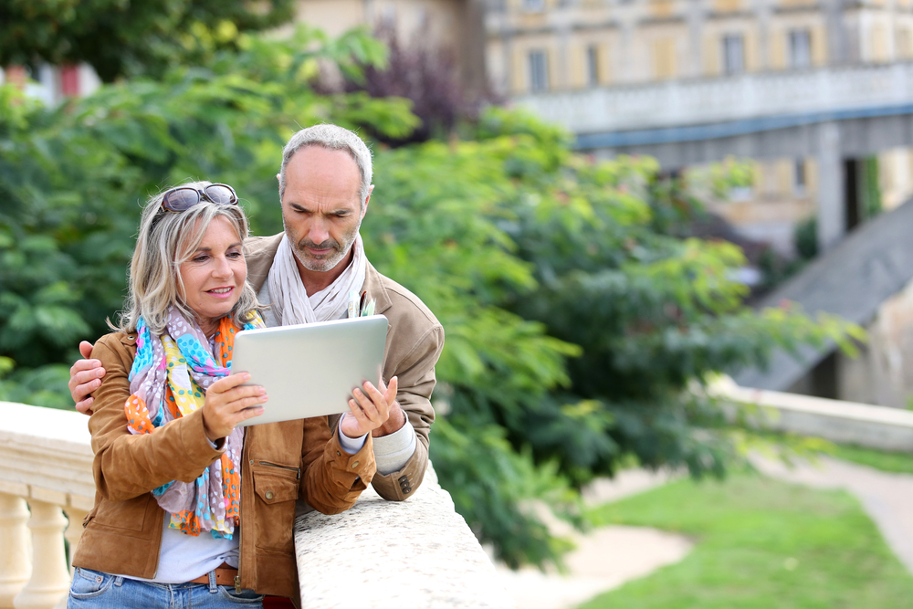 Older couple travelling looking on internet retirement planning