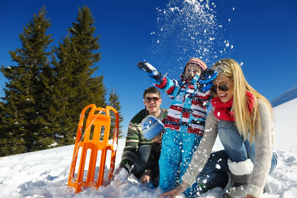 family enjoying winter staycation ideas by tobogganing and playing in the snow
