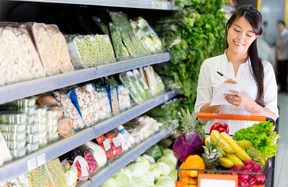 Woman in grocery store using a grocery list to save money on groceries