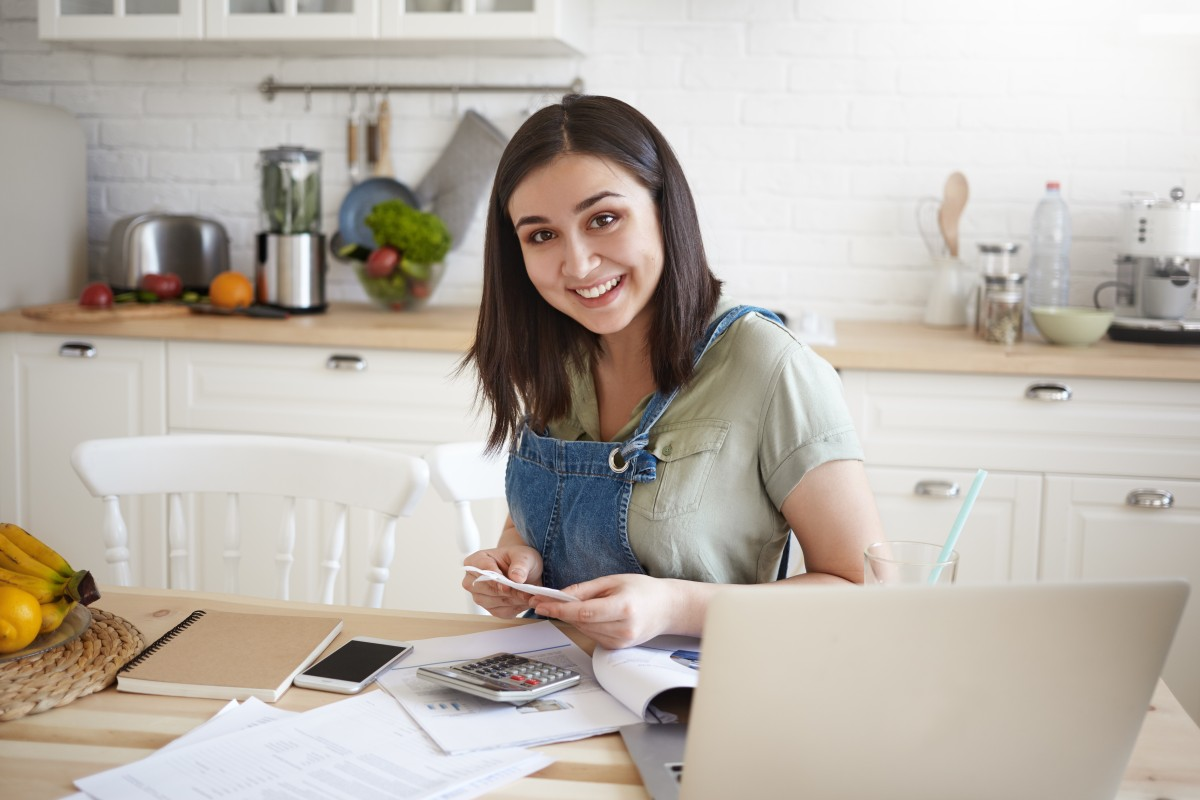 young woman sitting at kitchen table with laptop and calculator setting SMART financial goals